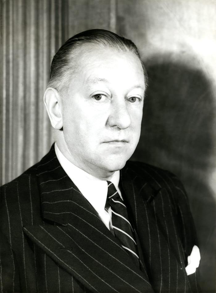 Black and white portrait of Allan Walton in a striped suit and tie posed sideways looking into the camera.