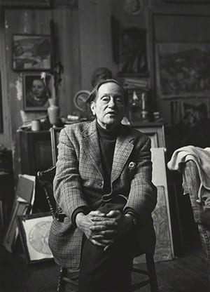 Black and white portrait of Duncan Grant sitting on a chair looking at the camera