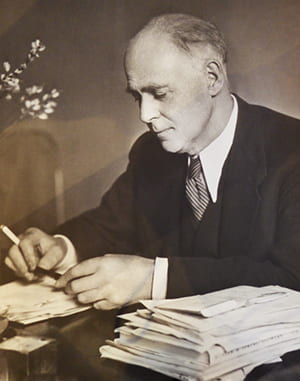 Black and white portrait of James Hogan over a pile of papers