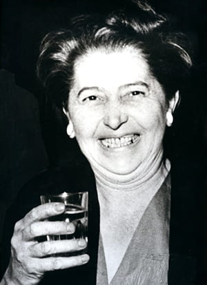 Black and white photo of Margaret Leischner holding a drink and smiling at the camera