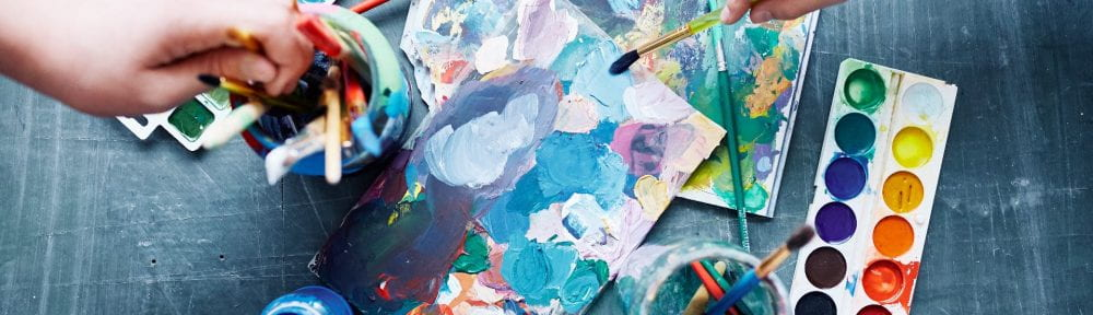 Children with paintbrushes beginning to create