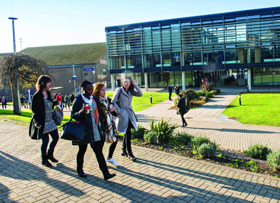 Group of students walking across Falmer campus in sunshine