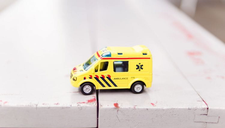 Close up of a toy ambulance on wooden tablee