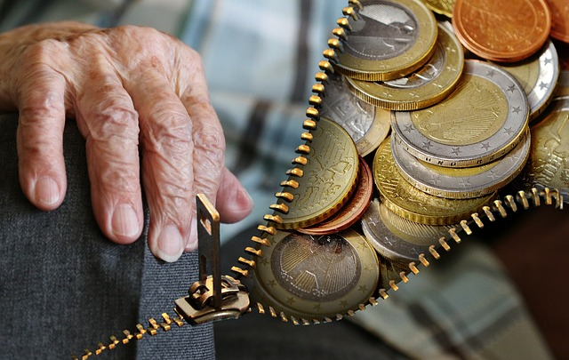 Image with an old persons hand, the image is split with a zip and behind it is coins and money.