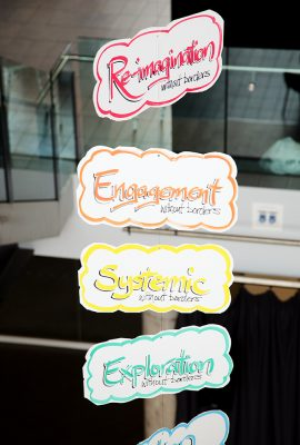 Signs strung from the ceiling reading 're-imagination', 'engagement', 'systemic', 'exploration'