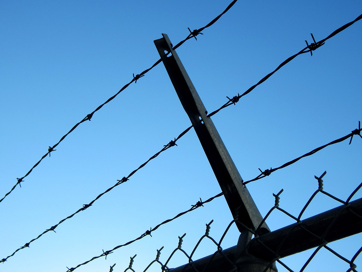 Blue sky behind a barbed-wire fence
