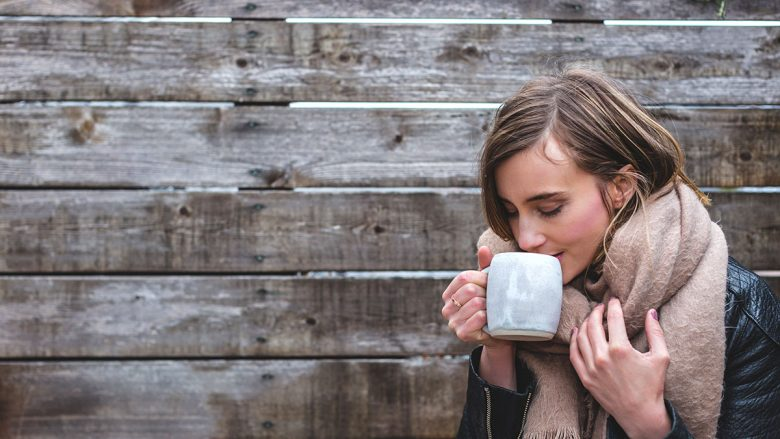 A woman drinking from a mug