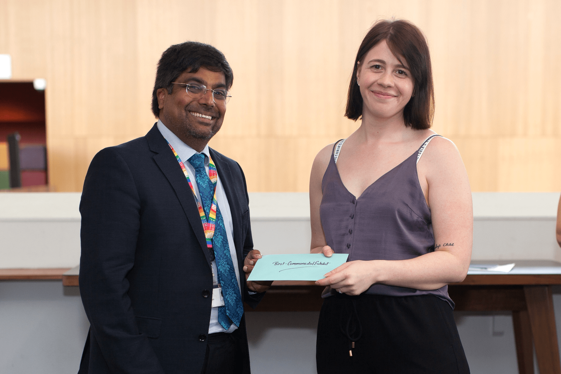 Professor Nishan Canagarajah presenting Laura Fox with the 'Best-Communicated Exhibit' prize