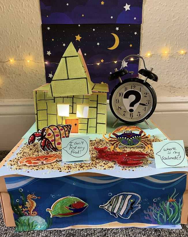 Two cartoon sea creatures standing in front of a cardboard house (lit from inside) and a clock (with part of its face covered by a question mark). Behind this arrangement is a poster featuring a night sky. The left-hand creature is saying 'I can't find any food'. The right-hand creature is saying 'Where is my soulmate?'.