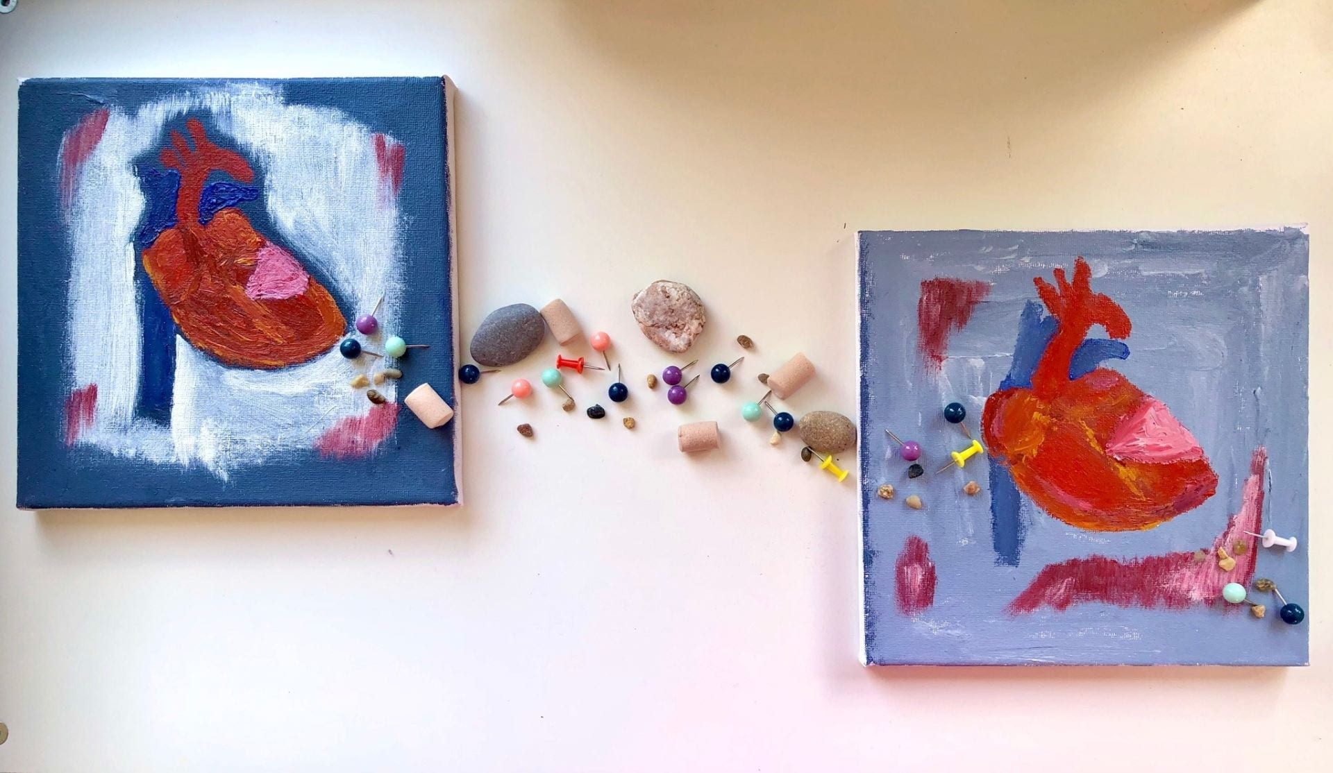 Two square paintings of hearts. Between them is an assortment of stones, earplugs and drawing pins.