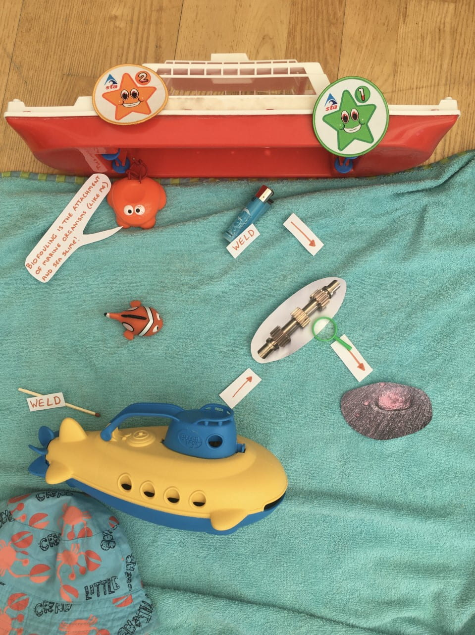 A toy boat with a towel beneath it. On top of the towel, which is intended to look like the sea, are: a lighter (labelled 'weld'); a toy frog (which is saying 'biofouling is the attachment of marine organisms (like me) and sea slime!); some toy fish; a metal gear; a toy submarine; a shell. Next to the submarine is a match (labelled 'weld').