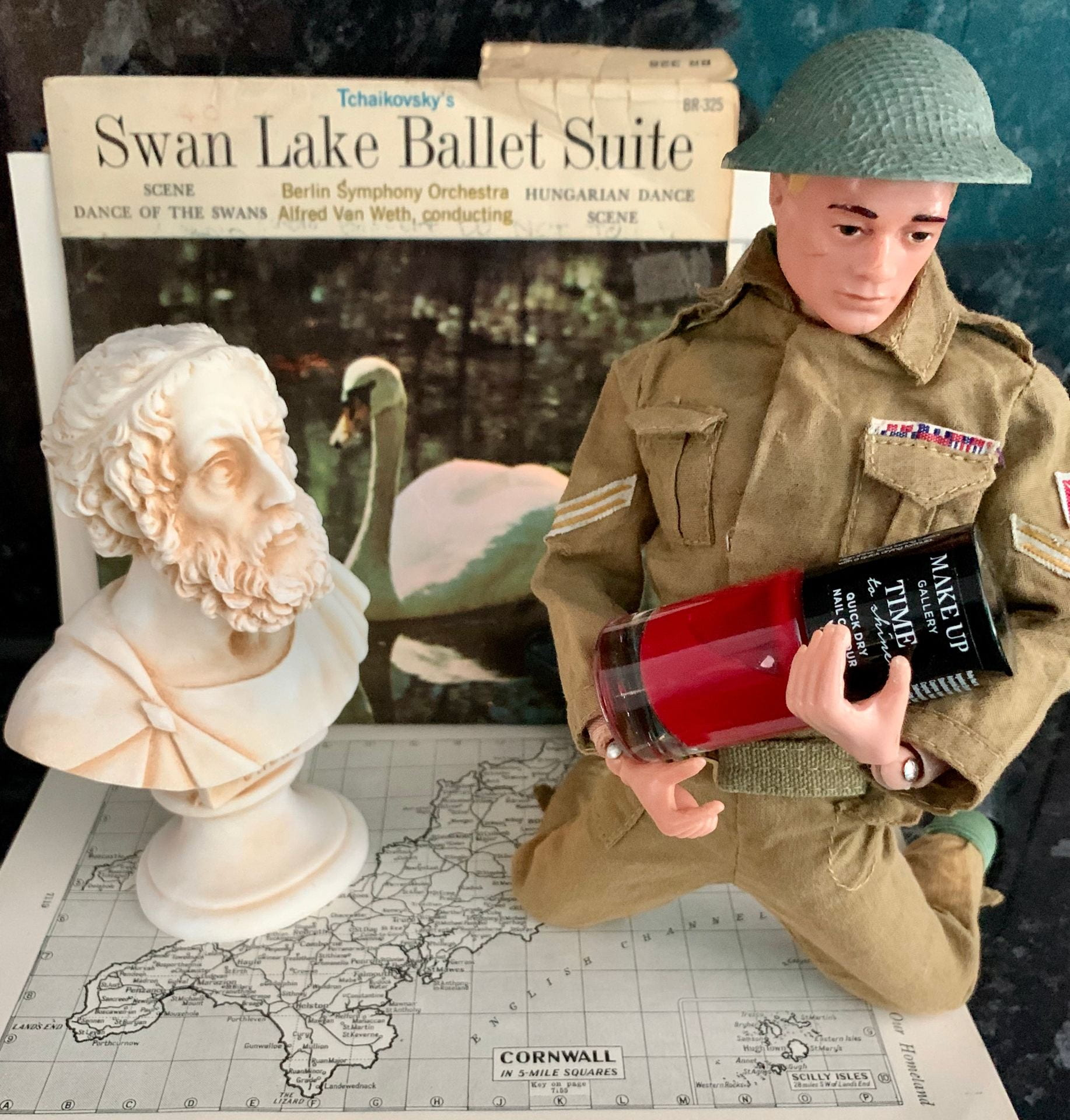 A classical bust and an 'Action Man' toy (holding nail varnish) on top of a map of Cornwall. Behind them is a the sleeve of a vinyl record: Tchaikovsky's Swan Lake Ballet Suite.