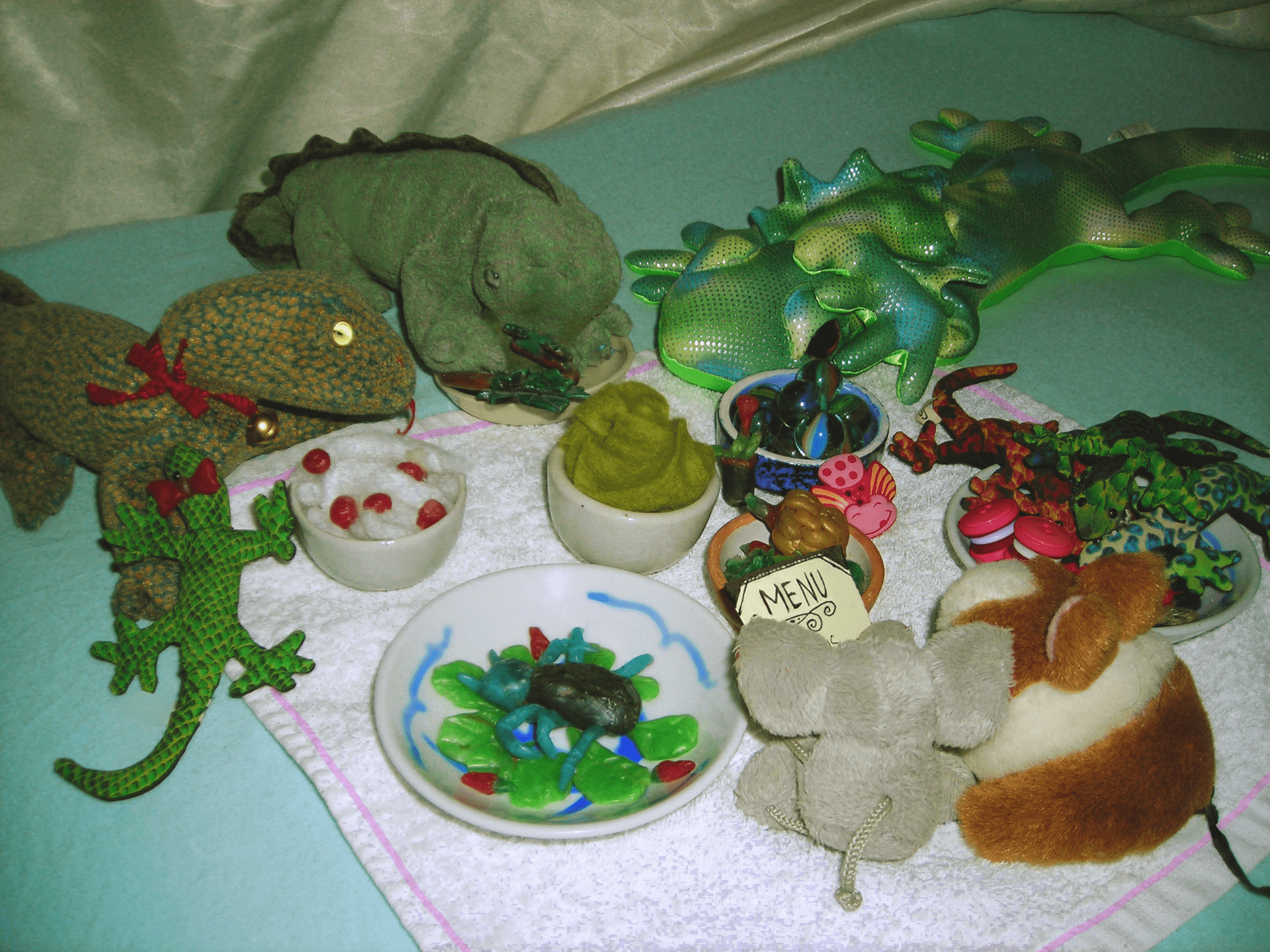 A selection of toy lizards enjoying a picnic.