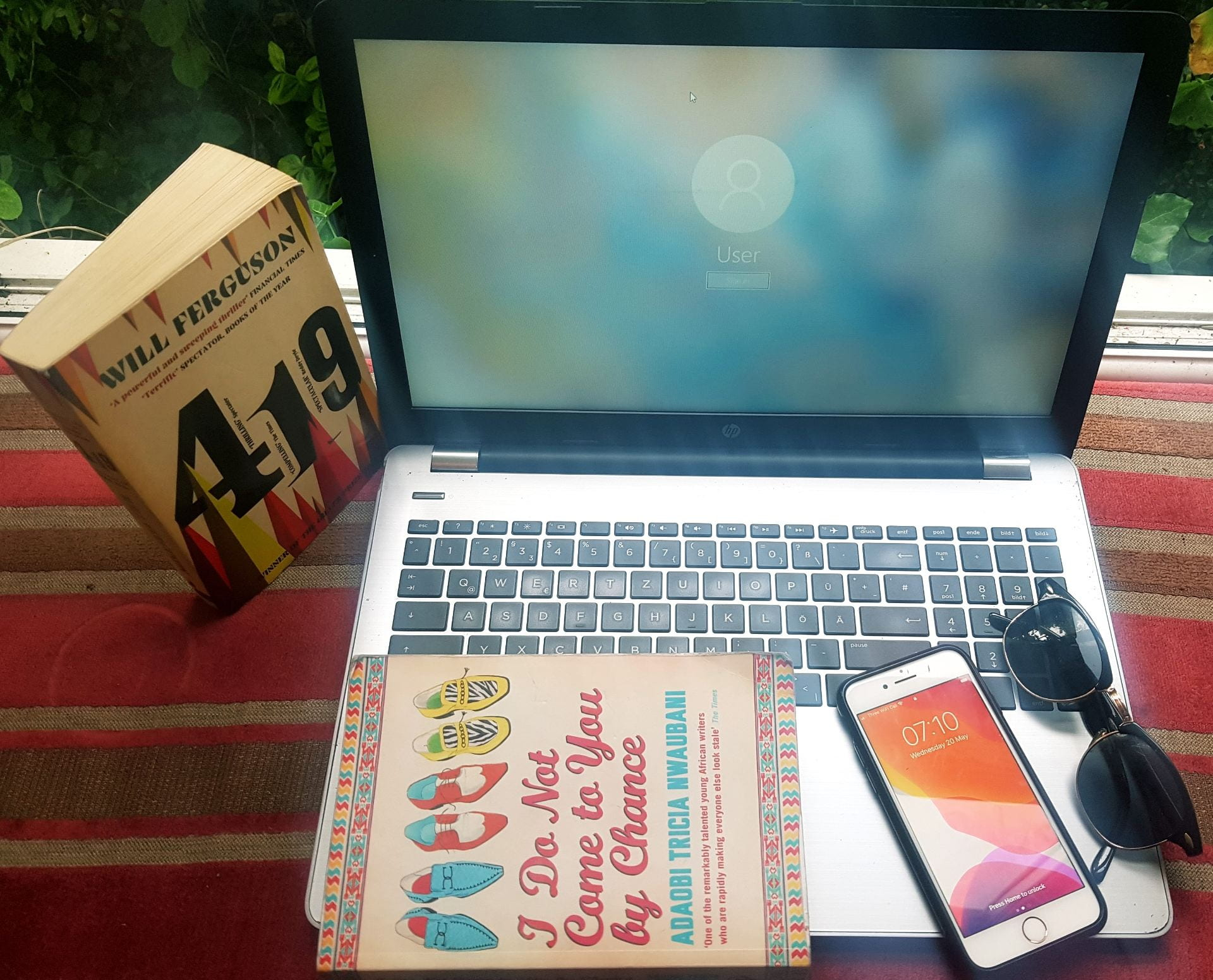 A MacBook laptop. On top of it is a novel ('I Do Not Come to You by Chance' by Adaobi Tricia Nwaubani), an iPhone and a pair of sunglasses.. To the left of the MacBook is another novel: '419' by Will Ferguson.
