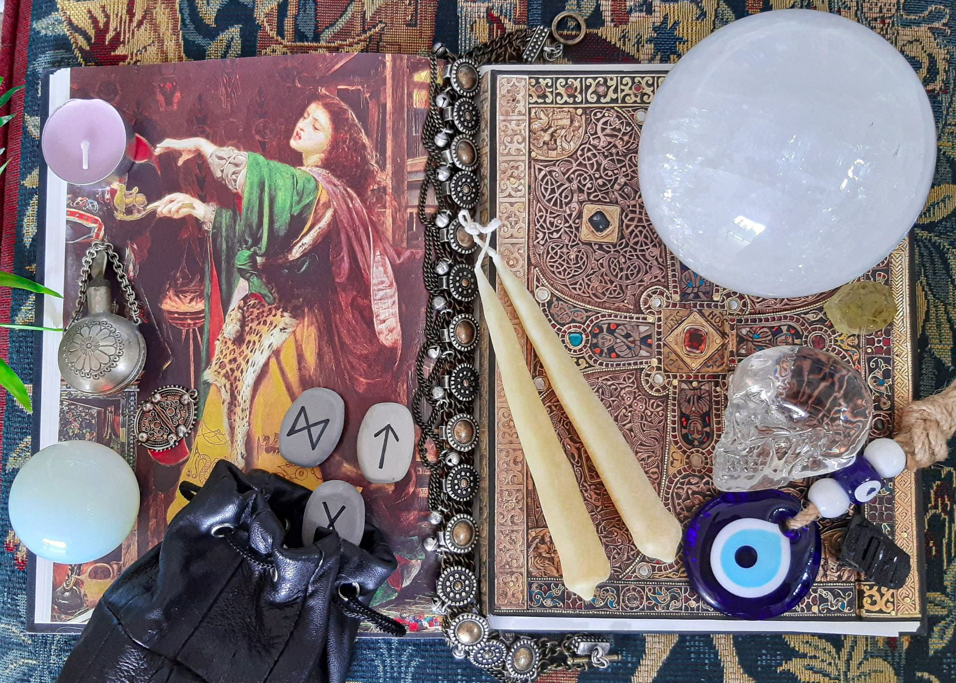 An antique book open on an illustration of a woman. On top of the book are a selection of objects: candles, an open bag of runes; a large, opaque crystal sphere; a transparent crystal skull.