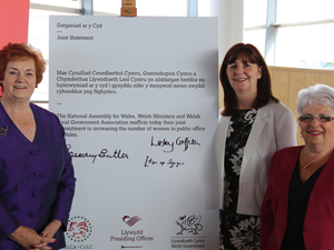 Three women with written statement expressing the commitment of The National Assembly for Wales, Welsh Ministers and Welsh Local Government to increasing the number of women in public office in Wales