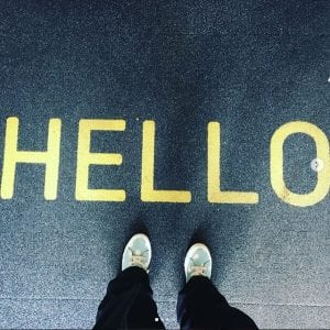 student's feet below the word 'hello'