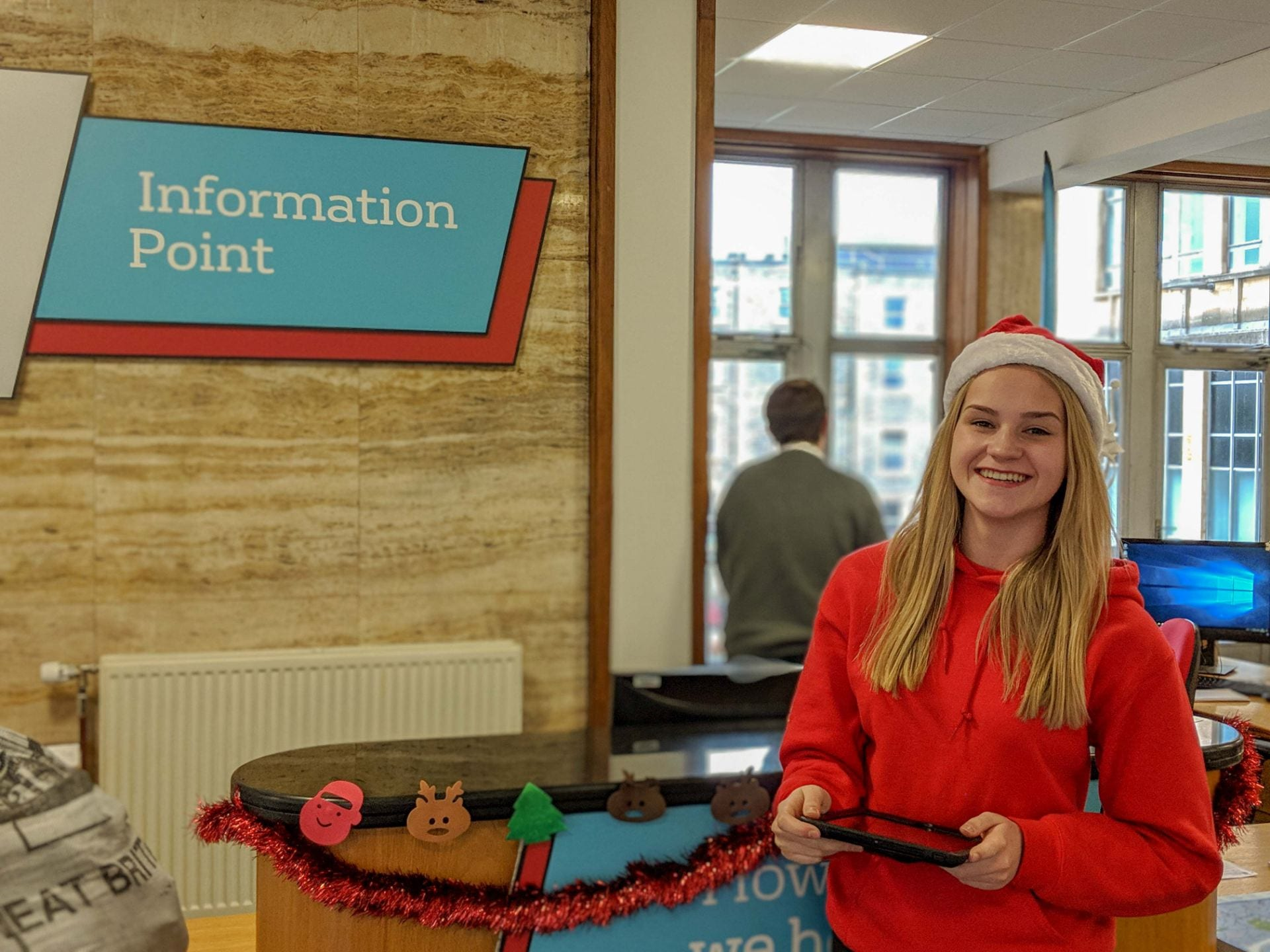 Olivia stands in front of the Information Point desk with an iPad in her hands