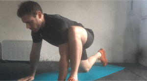 Fitness instructor demonstrates the first stage of the hip opener stretch by assuming a lunch position with one knee touch the floor behind and one foot extended forward. Hands are palm facing down on the floor next to the front foot.