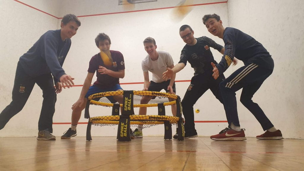 Five male students a stood in a squash court, gathered in a semi-circle around a roundnet. The roundnet is yellow and resembles a small trampoline. The group look like they are having fun.