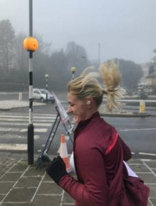 A lady running in a maroon coloured jacket