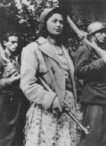 Black and white image of a woman in a dress and jacket, carrying a gun over her arm. Two men in the background also carry guns. They are all looking off camera, with calm expressions.