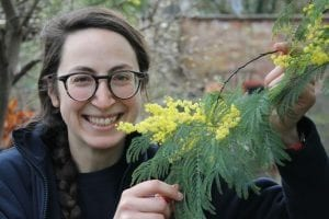 Irene Cambi, A woman with her hair in a plait and wearing glasses, smiles broadly. She is holding the foliage of a yellow feathery plant, Acacia dealbata.