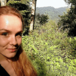 A photo of Dr Sandra Neumann, a white woman with long blond hair against a green background of trees.