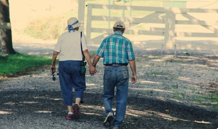 An older woman and older man wearing jeans shirts and hats walking along a gravel path on a sunny day, holding hands.