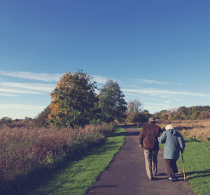 Photo of an older man and woman linked arms, walking down a path. Trees and blue sky in the background.