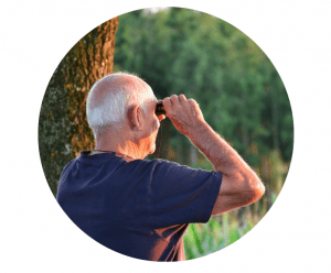 Circle cropped photo of an older man with grey hair looking through binoculars. A tree trunk and trees are in the background.