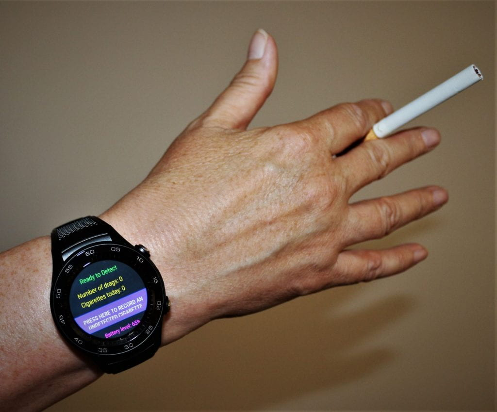 Hand and wrist wearing stopWatch and holding a cigarette