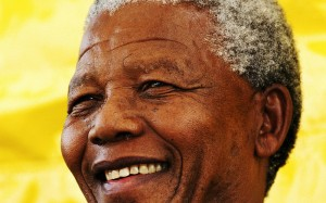 Image of Nelson Mandela's face smiling against a yellow background. Licence: Attribution-NonCommercial-NoDerivs 2.0 Generic. Source: https://secure.flickr.com/photos/presidenciard/
