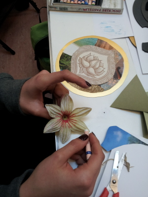 Person painting a flower in an artistic history workshop.
