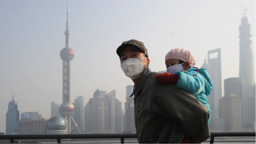 A man and child wear masks to visit Shanghai's Bund. Via Creative Commons/CNN