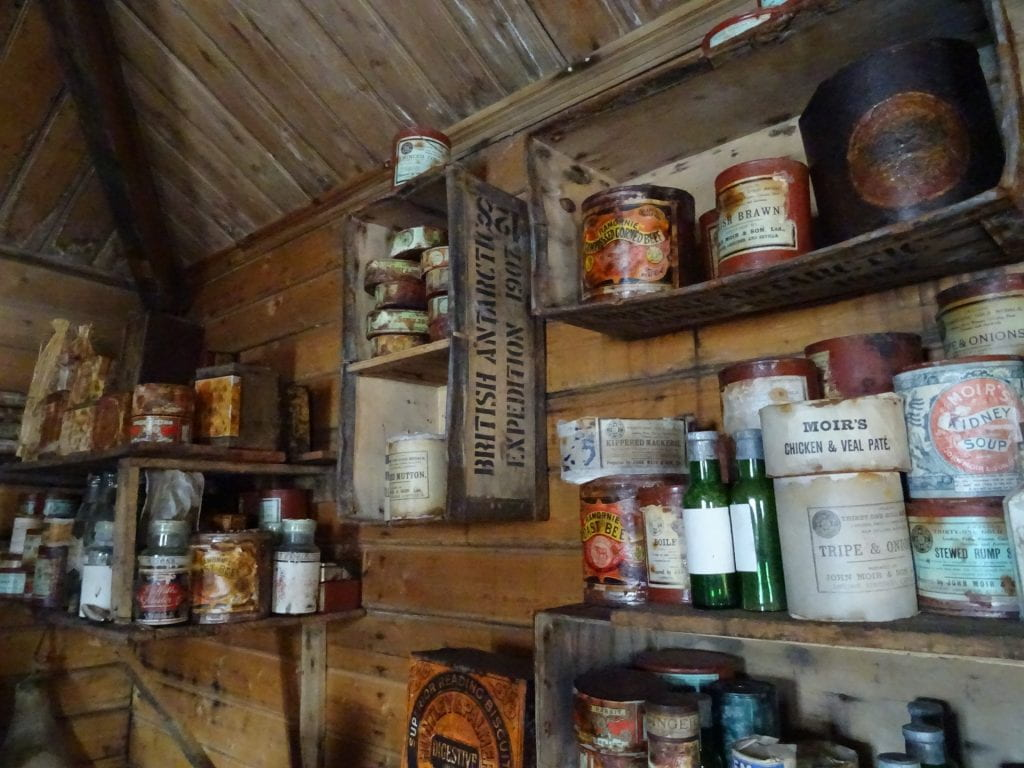 Photo of shelves in Shackleton's hut, stacked with tins and provisions