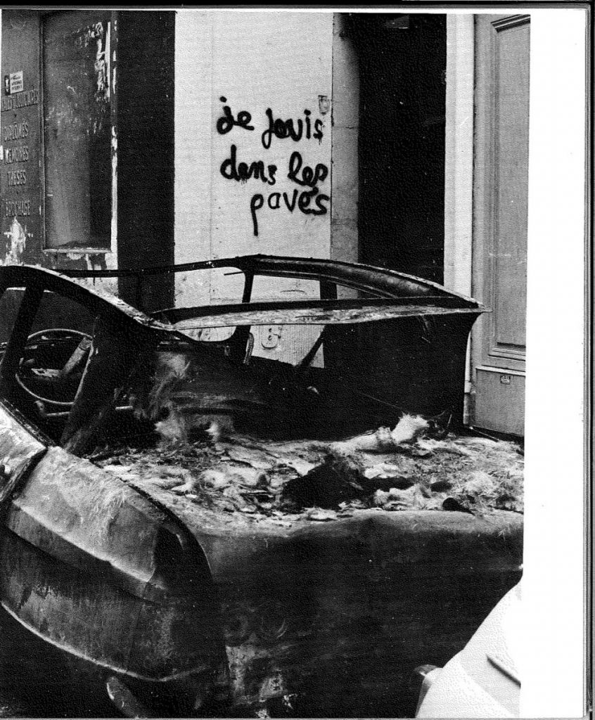 Black and white photo shows the wreckage of a car in the foreground and graffiti in the background reading 'je sevis dans les pavés'