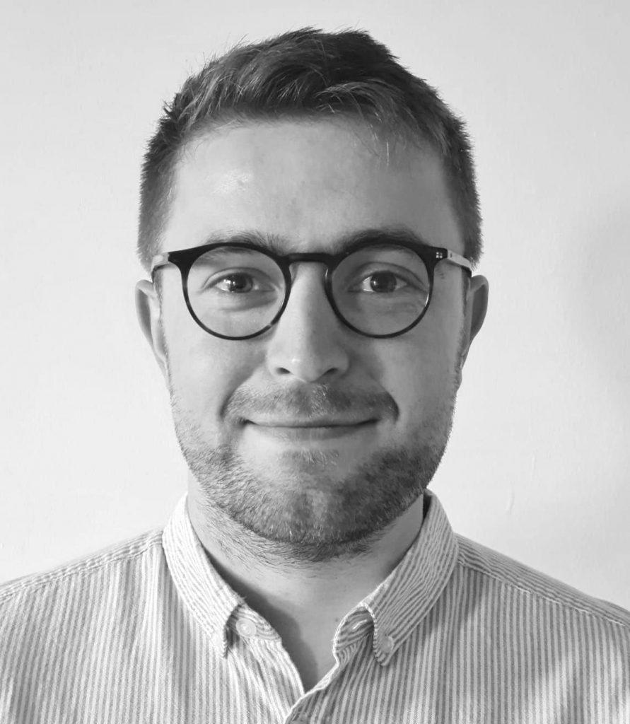 Black and white portrait of Dan Booker, wearing glasses