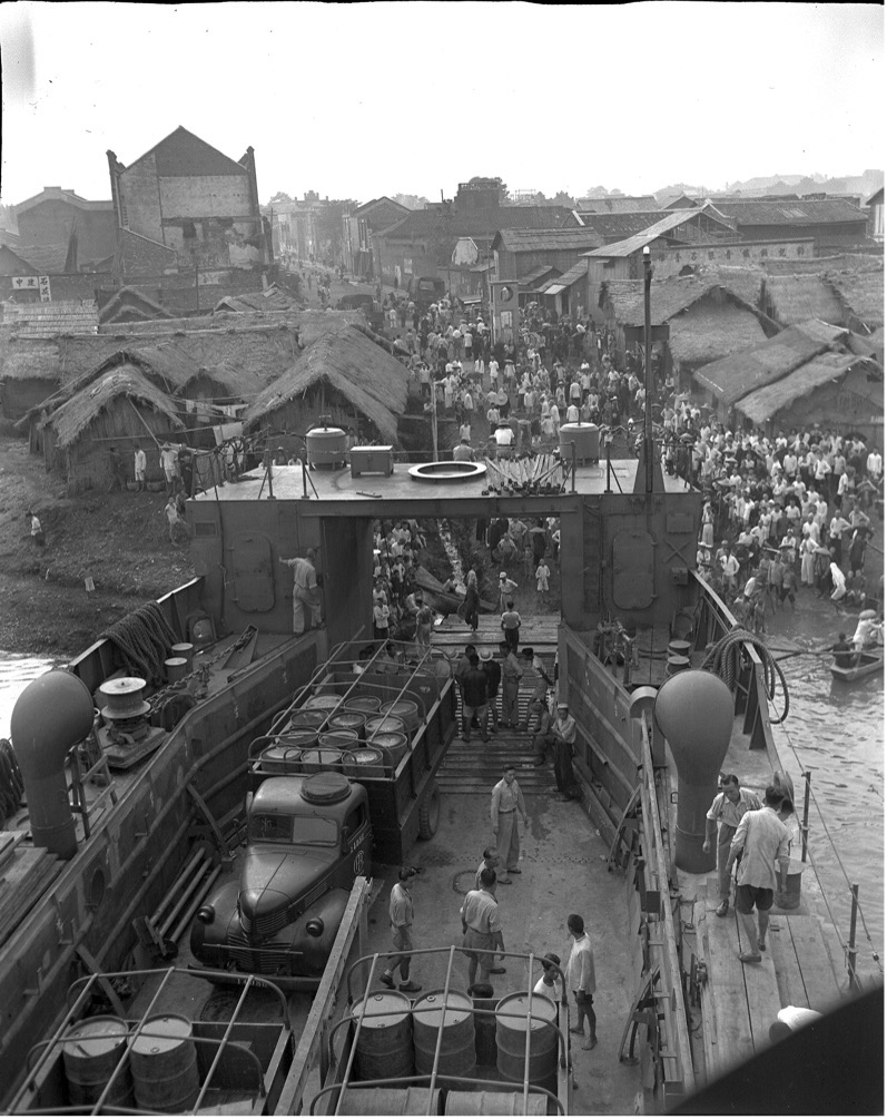 Black and white photo of trucks being unloaded
