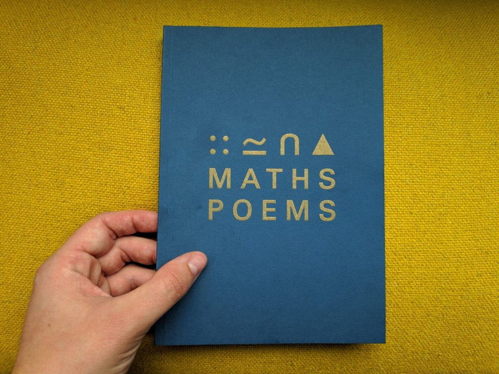 "A image of a hand holding the ""maths poems"" anthology against a yellow backdrop. the book is blue with symbols and the words ""Maths Poems"" in Gold font."