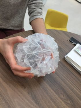 image of hands holding an angular sphere made from folded plastic.