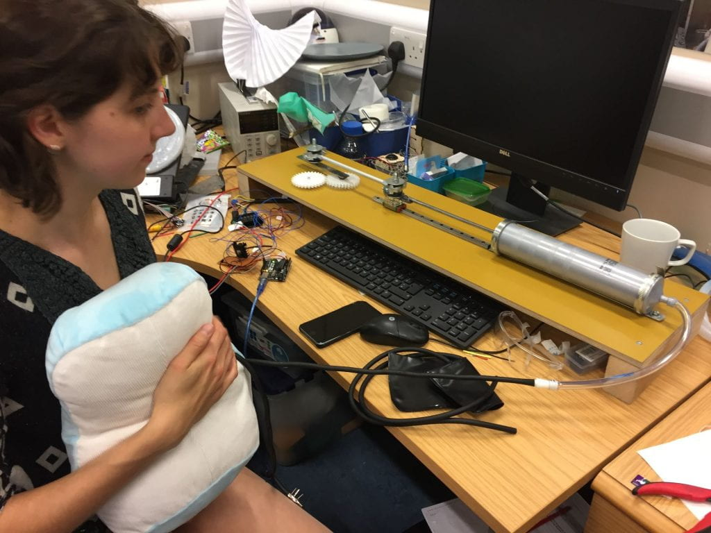 Image of a girl at a desk holding a mechanical pillow with a pump attached.