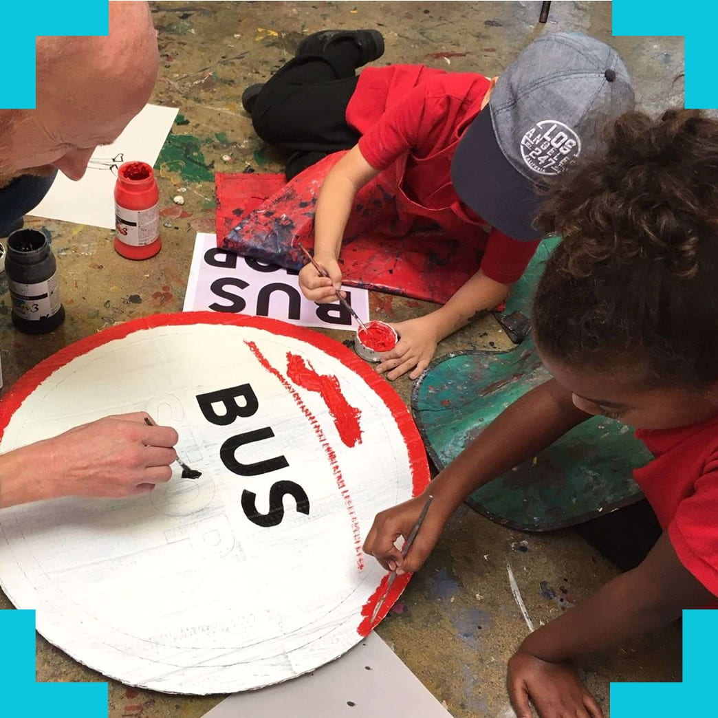 children painting a buc stop sign
