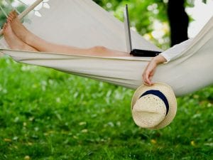 Personal relaxing with laptop in a hammock