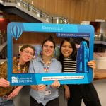 Students and staff at the Global Food Festival holding a social media frame