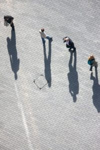 people walking on pavement and their shadows