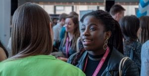 A photograph of Kofo Ajala at a Careers Fair smiling and talking to someone who is facing away from the camera