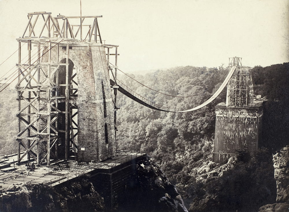 A view of Clifton Suspension Bridge, Bristol, from St Vincent's Rocks, showing the piers under construction, along with chains, and scaffolding on the towers. DM216/3/4.