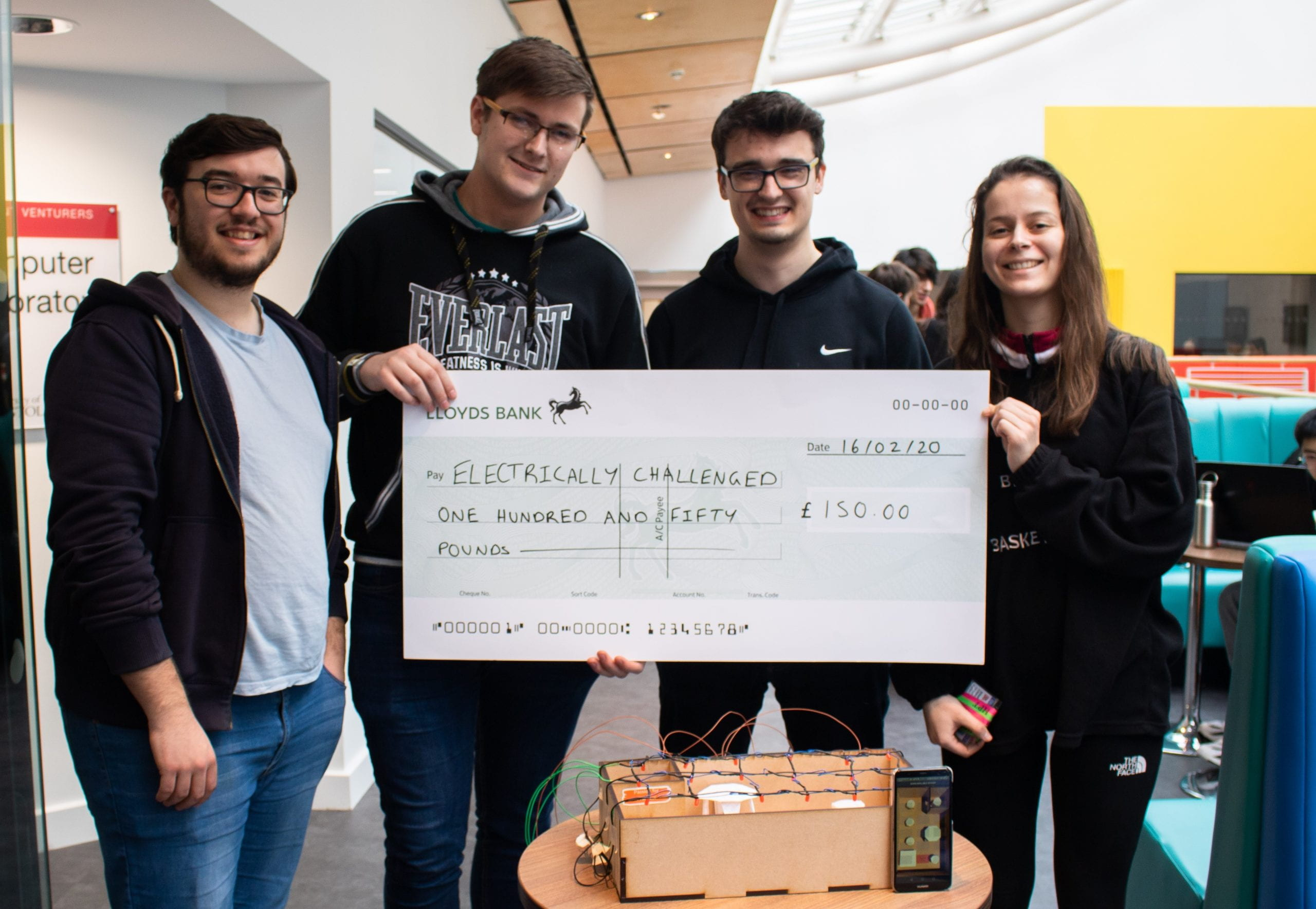 four students with a giant cheque and a model factory