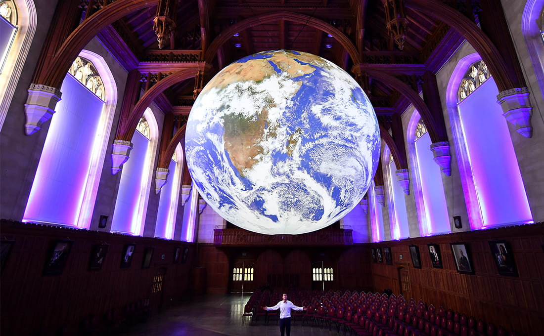 Artist Luke Jerram stands underneath a replica of the earth